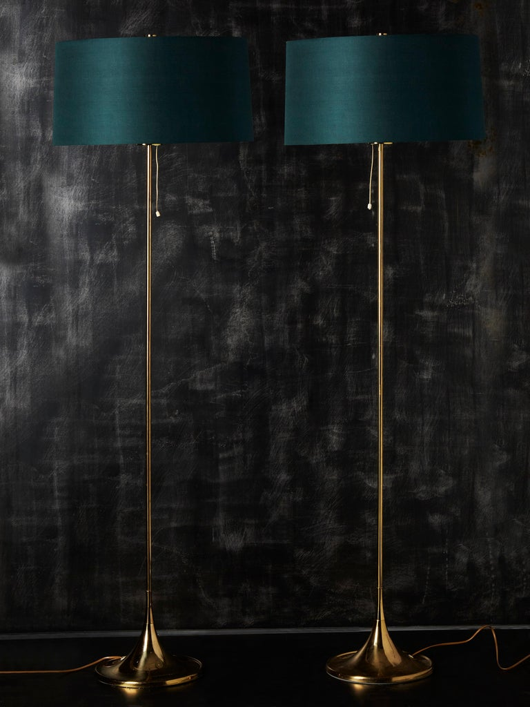 Pair of floor lamps made of a brass trumpet shaped foot and central stem, topped with a dark green shade and a white Plexiglass light diffuser.