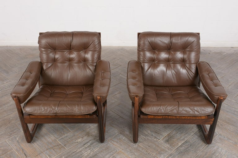 This pair of 1960's Danish Leather Lounge Chairs by Oddvar Vad is made out of solid rosewood with a patina finish and is professionally restored. These Bauhaus-style club chairs are upholstered in their original dark brown leather which is in great