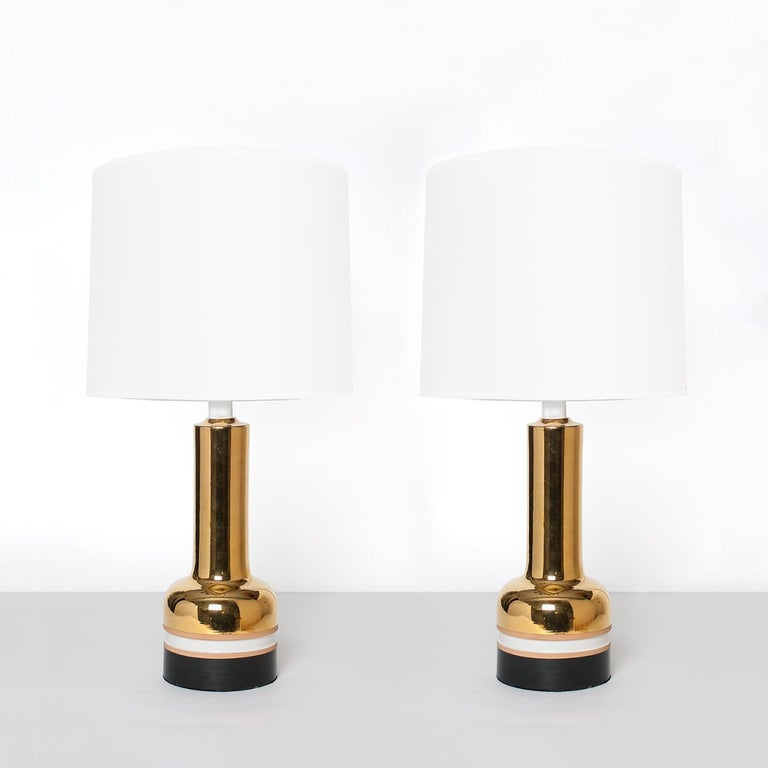 Pair of Scandinavian Modern ceramic table lamps with brilliant gold glaze made in Italy for Bergboms of Sweden. The lamps are detailed with unglazed and glazed bands in black and white. Newly re-wired for the USA with polished brass double socket