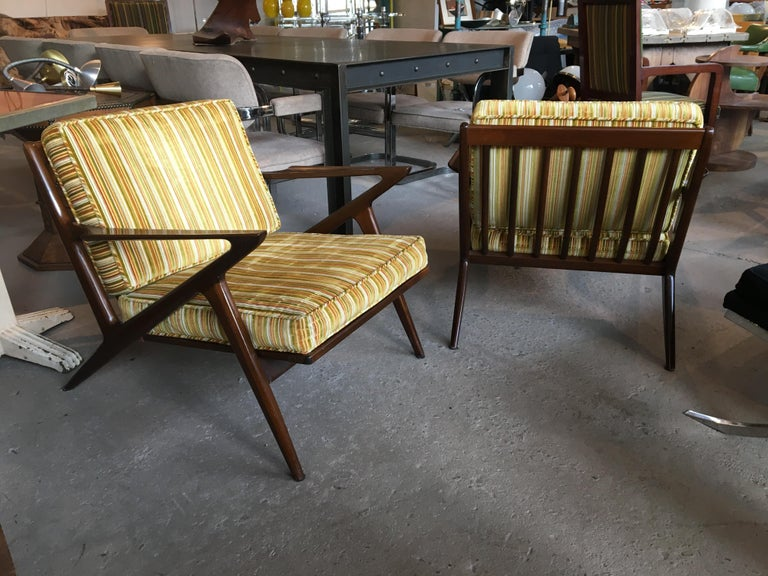 Pair of original walnut Z chairs, designed by Poul Jensen for Selig, circa 1960s. Both chairs retain their original Selig made in Denmark metal mark. Wood has great rich color, and webbing in very good condition. Cushions in vintage striped