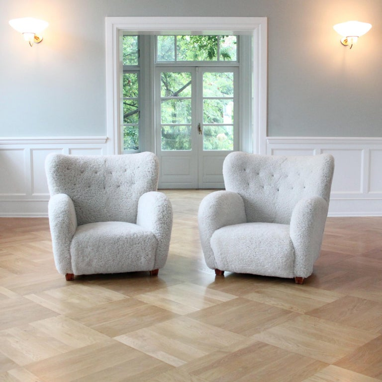 Scandinavian Modern, Finland, 1950s.  A magnificent sculptural pair of Mid-Century Modern armchairs, manufactured by Haimi, Finland, 1950s.  The armchairs have been reconditioned with new upholstery in luxurious off-white shearling and dark