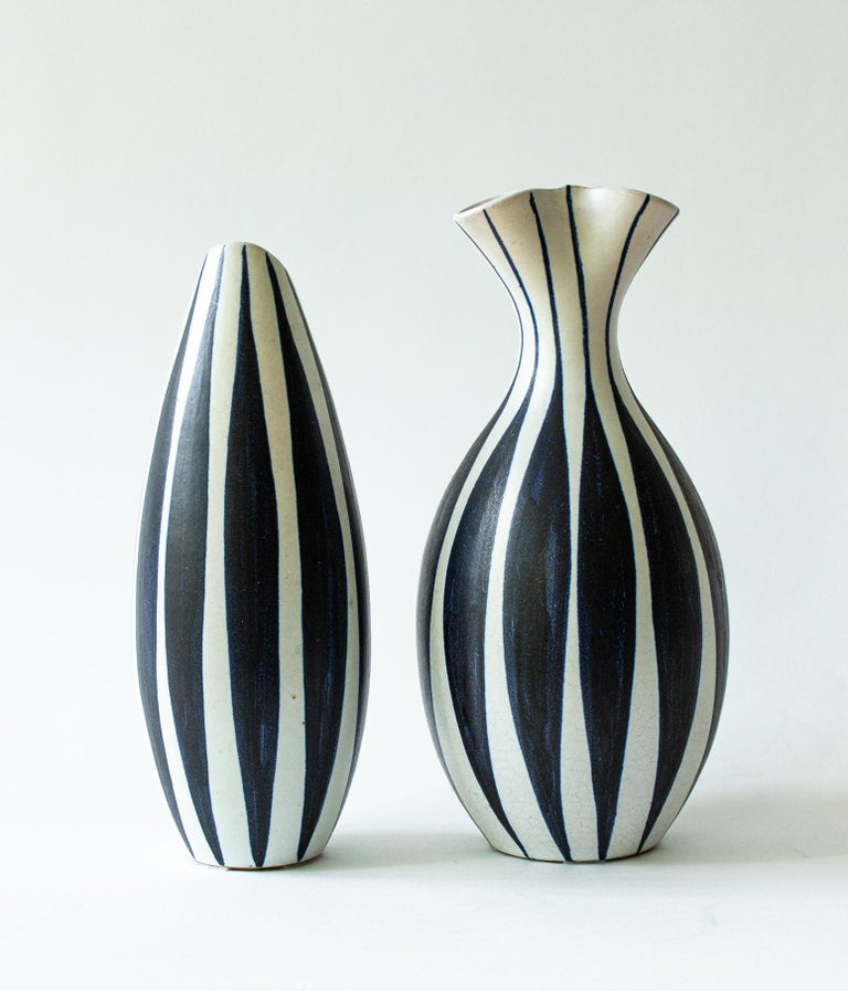 A pair of Scandinavian Modern vases with stripes in dark blue and white. Made by Mette Doller and Ivar Eriksson for Hoganas, Höganäs.