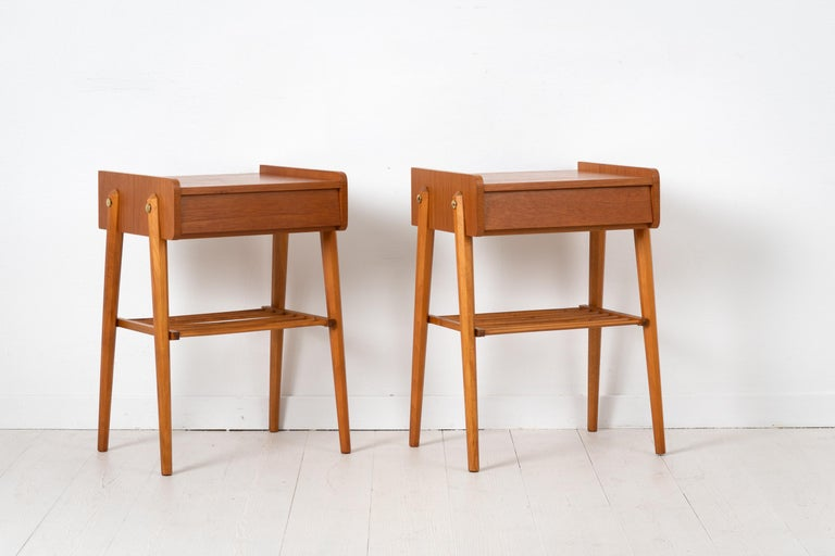 Scandinavian modern teak nightstands from the mid 20th century. The pair are designed and made in Sweden and have a single large drawer as well as a ribbed shelf. A decorative detail is the brass hardware. Marked AB BJÄRNI Bjärnum which is a Swedish