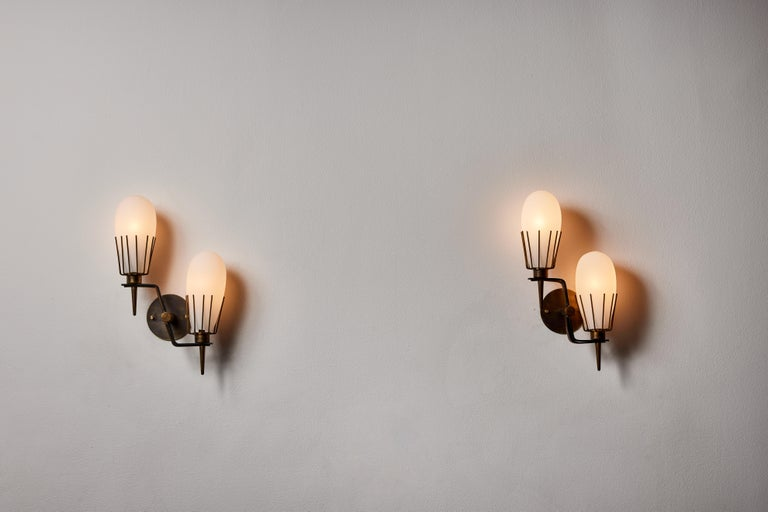 Pair of sconces by Arredoluce. Manufactured in Italy, circa 1950s. Brushed satin glass diffusers, brass, custom brass backplate. Rewired for U.S. standards. We recommend two E14 25w maximum bulbs per fixture. Bulbs provided as a onetime courtesy.