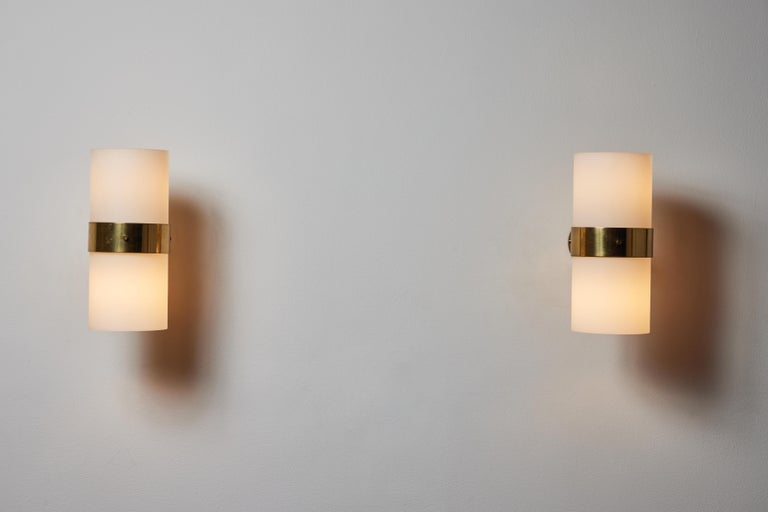 Pair of sconces by Candle. Manufactured in Italy, circa 1960s. Opaline glass diffuser, brass hardware. Custom brass backplates. Rewired for U.S. standards. We recommend two E26 bulbs per sconce Bulbs provided as a one time courtesy.