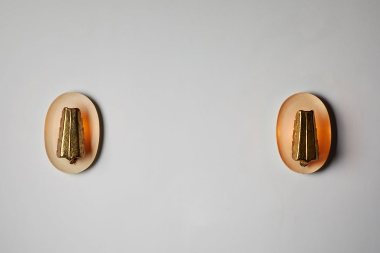Pair of sconces by Giuseppe Ostuni for Oluce. Designed and manufactured in Italy, circa 1950s. Lacquered wood and hand worked brass. Wired for US junction boxes. Each light takes one E14 75w maximum European candelabra bulb.