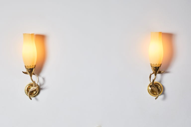 Pair of sconces by Paavo Tynell for Idman Oy. Designed and manufactured in Finland, circa 1940's. Opaque glass diffusers, brass hardware. Custom brass backplates. Rewired for US junction boxes. Each sconce takes one E27 75w maximum bulb.
