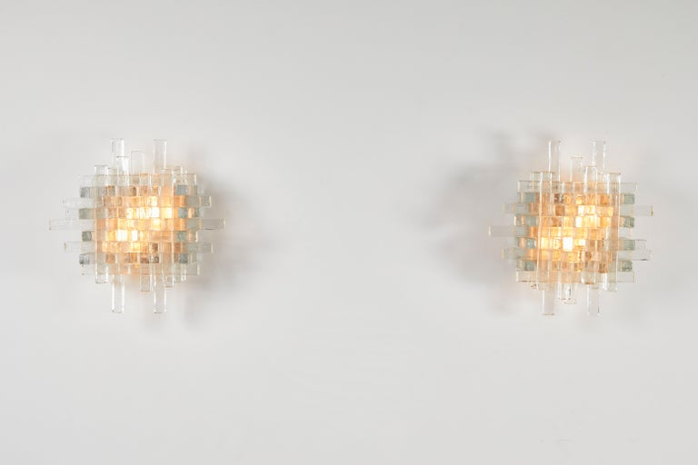 Pair of sconces by Poliarte. Manufactured in Italy, circa 1960s. Textured glass, metal frame. Rewired for U.S. junction boxes. Each light takes two 40W maximum bulbs. Bulbs provided as a one time courtesy.