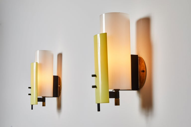 Pair of sconces by Stilnovo. Manufactured in Italy, circa 1960s. Acrylic and brass. Custom brass backplates. Each sconce takes one E27 25W maximum bulb. Bulbs are provided as a one time courtesy. Qty: 2 sconces with yellow front shades and Qty: 2