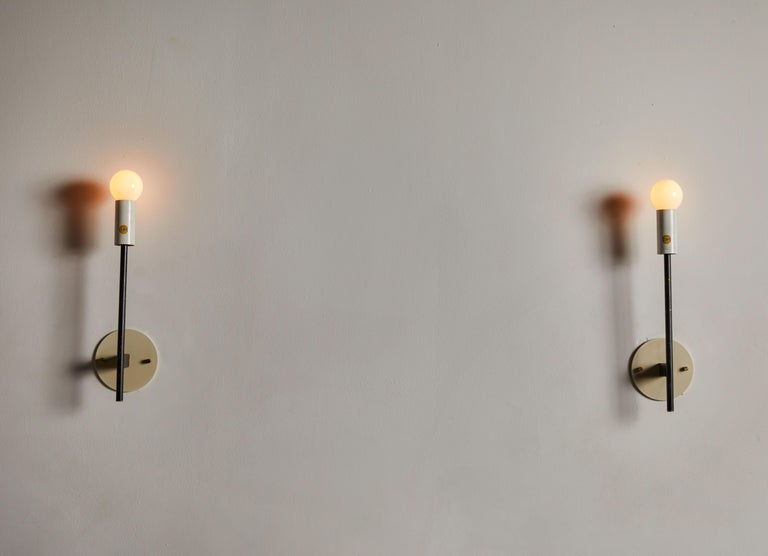 Pair of sconces by Stilnovo. Manufactured in Italy, circa 1950s. Brass and enameled aluminum. Rewired for US junction boxes. Maintains original manufacturer's label. Each sconce takes one E27 60w maximum bulb.