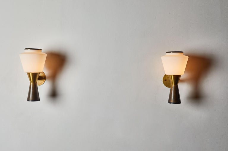 Pair of sconces by Stilnovo. Manufactured in Italy, circa 1960s. Patinated brass with brushed satin glass diffusers. Custom brass backplate. Rewired for US junction boxes. Each light takes one E27 60w maximum bulb.