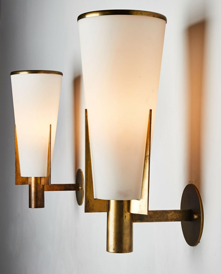 Pair of sconces by Stilnovo. Manufactured in Italy, circa 1950s. Brushed satin glass, brass. Rewired for US junction boxes. Each light takes one E27 60w maximum bulb. Maintains original manufacturer's label.