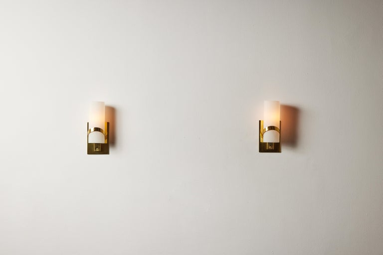 Pair of sconces by Stilnovo. Manufactured in Italy, circa 1950's. Brushed satin glass diffusers, brass. Custom brass backplate. Rewired for U.S. standards. We recommend one E14 candelabra bulb per fixture. Bulbs provided as a onetime courtesy.