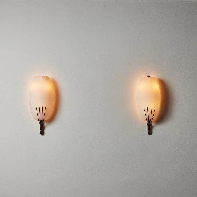 Pair of Sconces by Stilnovo. Manufactured in Italy, circa 1960's. Brushed satin glass, brass. Rewired for U.S. standards. We recommend three E12 bulbs 25w maximum bulbs per fixture. Bulbs not provided.