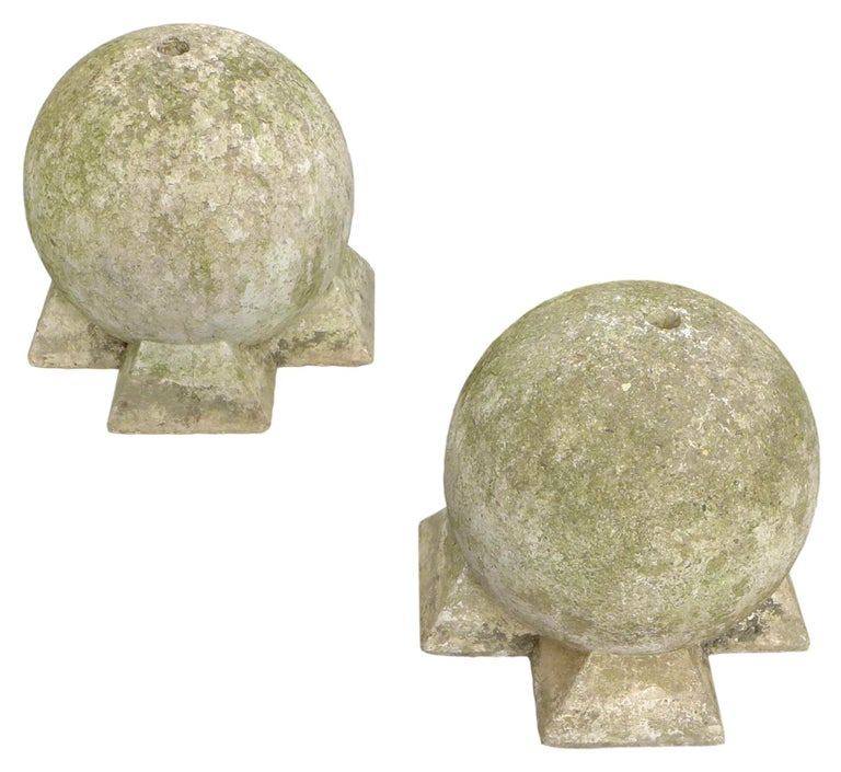 An incredible pair of sculptural, cast-stone spheres. Evocative, geometric forms of powerful scale and presence wearing an even, much-desired patina from a long life outdoors. A hole at the top of each sphere going deep into the form evincing some