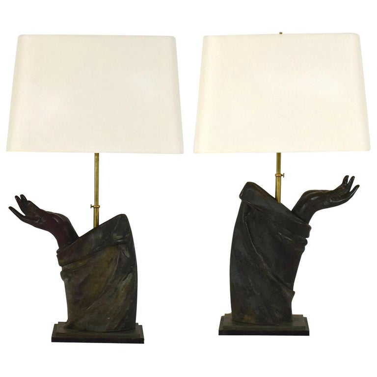 A sculptural pair of French bronze arm lamps with linen shades.