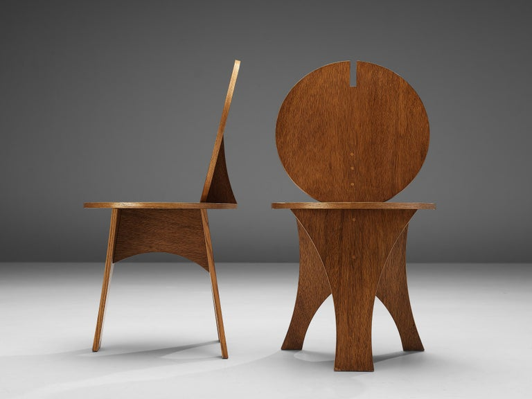 Set of side chairs, wood, Italy, 1970s.  Two sculptural side chairs with characteristic backrests. A flat circular backrest with a geometric gap on top highlights the rare appearance of these two side chairs. The round shape is echoed in the round
