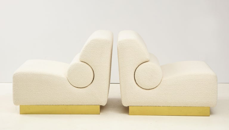 Impressive pair of ivory bouclé sculptural lounge chairs or slipper chairs custom made in Florence, Italy. Superb craftsmanship and design lines. These large and roomy lounge chairs are extremely comfortable and sit atop a square brass plinth