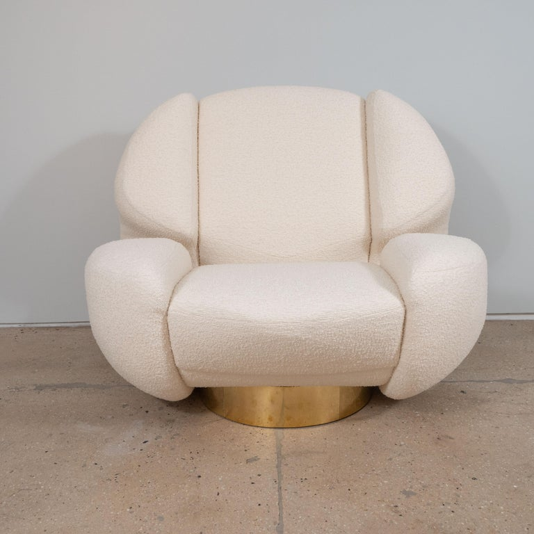 Impressive pair of ivory bouclé sculptural lounge chairs custom made in Florence, Italy. Superb craftsmanship and design lines. These large and roomy lounge chairs sit atop a round brass plinth (non-swivel). Upholstered in French Bisson Brunneel