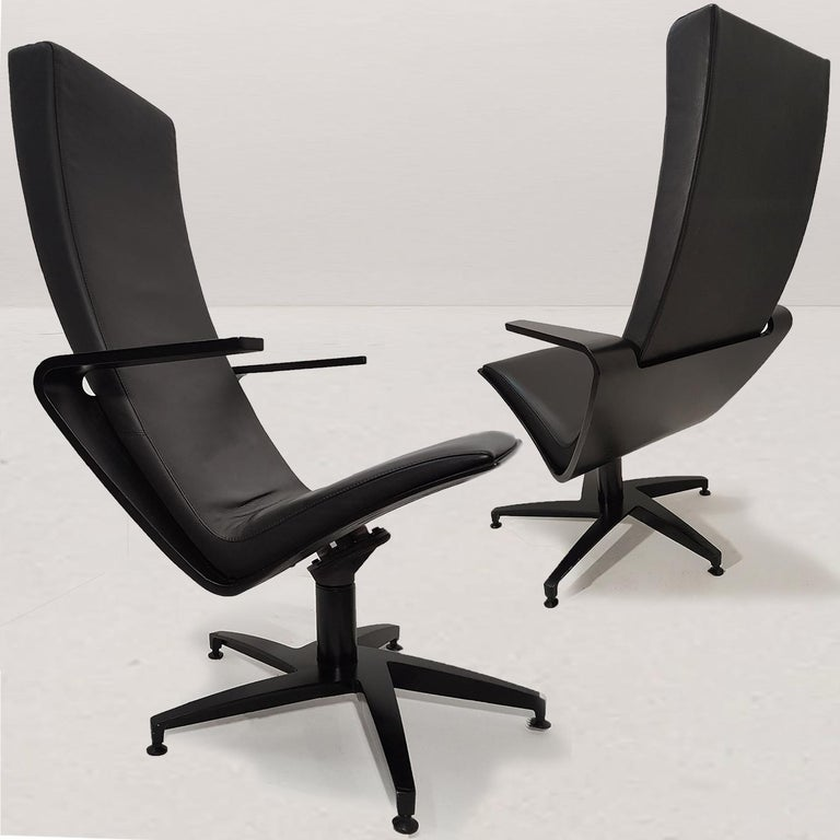 A pair of sculptural, swiveling lounge chairs. Base of black cast aluminium, seat shell of birch plywood stained in black. Damper mechanism under the seat. Upholstered with high-end quality black leather. Very comfortable seat.   Design Pentti