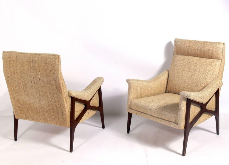 Pair of sculptural X-arm midcentury lounge chairs, American, circa 1960s. They look great from every angle and are very comfortable. These chairs are currently being refinished and reupholstered and can be completed in your choice of finish color