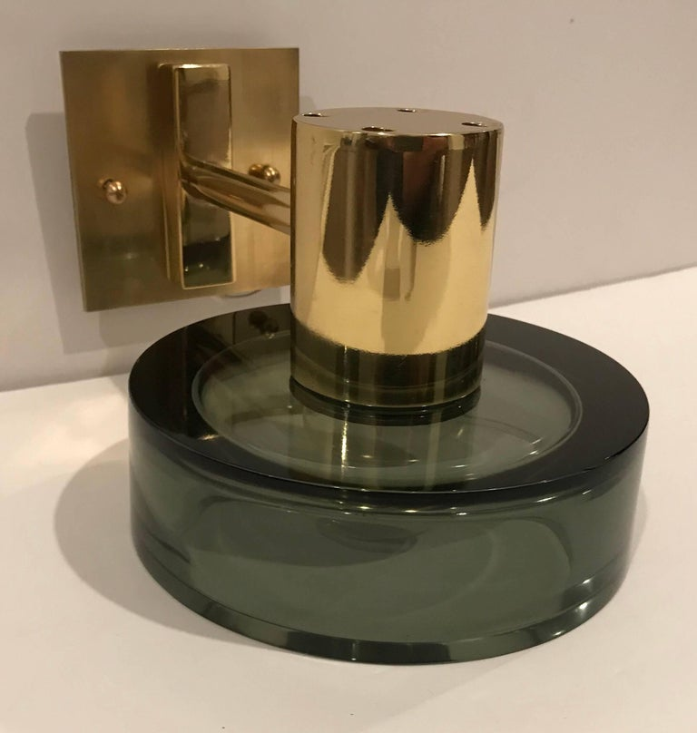A pair of 1960s wall lights composed of thick Murano glass olive green shades with golden polished brass fixtures and wall plates by Seguso. Newly rewired. Excellent shape.