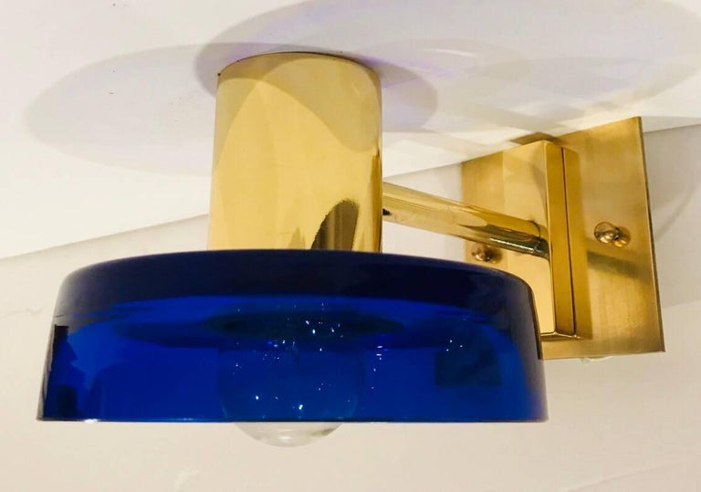 An original pair of 1960s wall lights with handblown thick blue Murano glass shades and golden brass fixtures