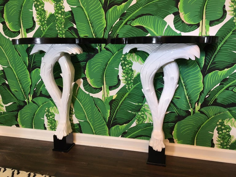 Pair of solid wood, hand-carved Serge Roche demi-lune console tables. Perfect example of Hollywood Regency / Dorothy Draper style. Each table mounts to wall with built in wood cleat, and stands 34.75