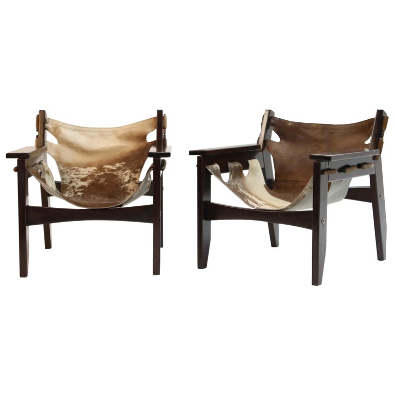 A charming pair and wonderful examples of 'Kilin' chairs by famed Brazilian modern designer Sergio Rodrigues for Oca in 1970s Brazil. Frame is a succulent Brazilian Rosewood and the leather slings are hair-on cowhide. The pattern on each sling is