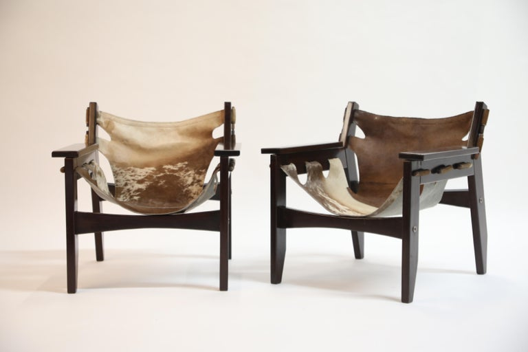 A charming pair and wonderful examples of Kilin chairs by famed Brazilian modern designer Sergio Rodrigues for OCA in 1970s Brazil. Frame is a succulent rosewood and the leather slings are hair-on cowhide. The pattern on each sling is slightly