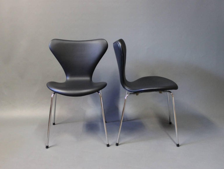 A pair of seven chairs, model 3107, designed by Arne Jacobsen and manufactured by Fritz Hansen in 1967. The chairs have recently been upholstered in classic black leather.