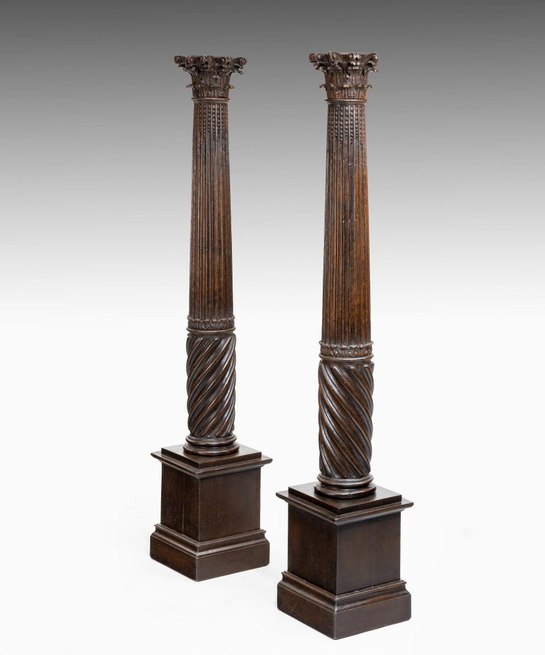 A wonderfully atmospheric pair of 17th century carved oak columns; the composite capital raised on a fluted and spiral turned column which terminates in a modern pedestal base.