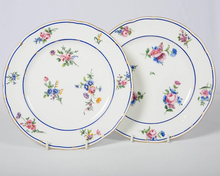 A pair of 18th century Sèvres Porcelain dishes made circa 1785. They are painted with exquisite sprays of flowers in soft pinks, blues, purple and yellow. The border and the edge are decorated with a fine enameled blue line alongside the most