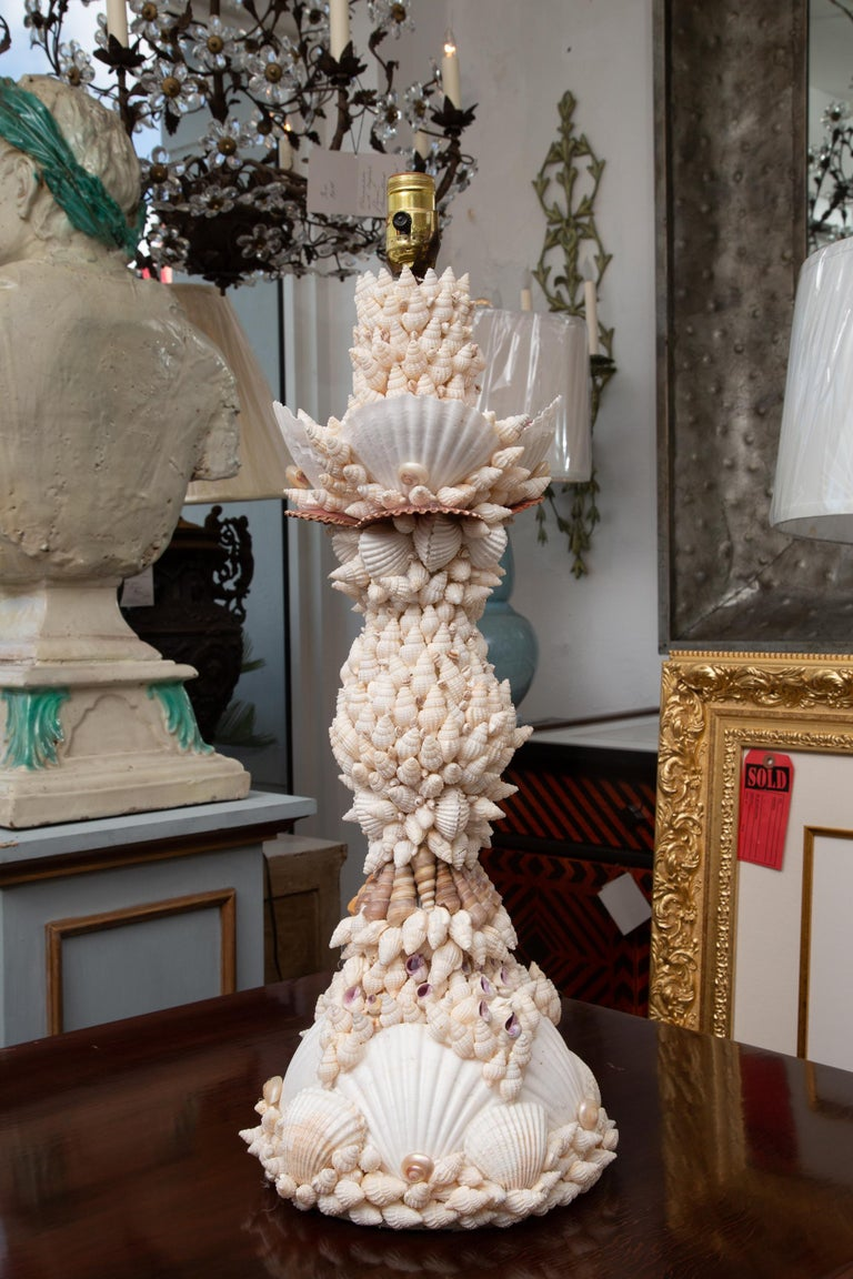 This is a pair of custom table lamps, encrusted overall with a variety of shells. 20th century.
