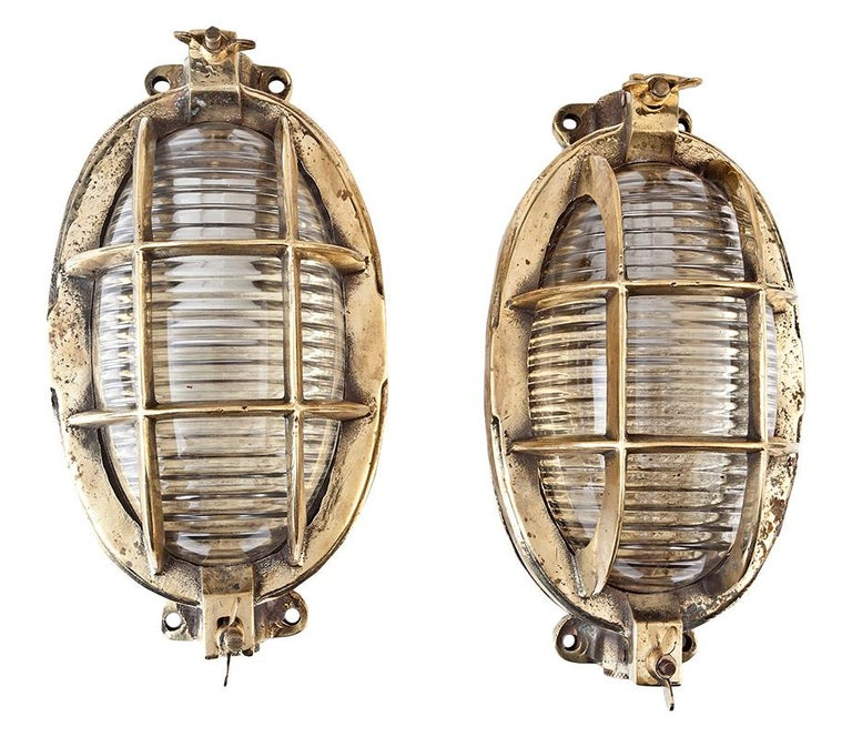 Pair of original ship's brass passageway lights with Fresnel lens glass shades. The overlying brass cage is hinged on one end and a dog latch on the opposite end gains access to the bulb. The socket takes a standard base light bulb. Rewired for