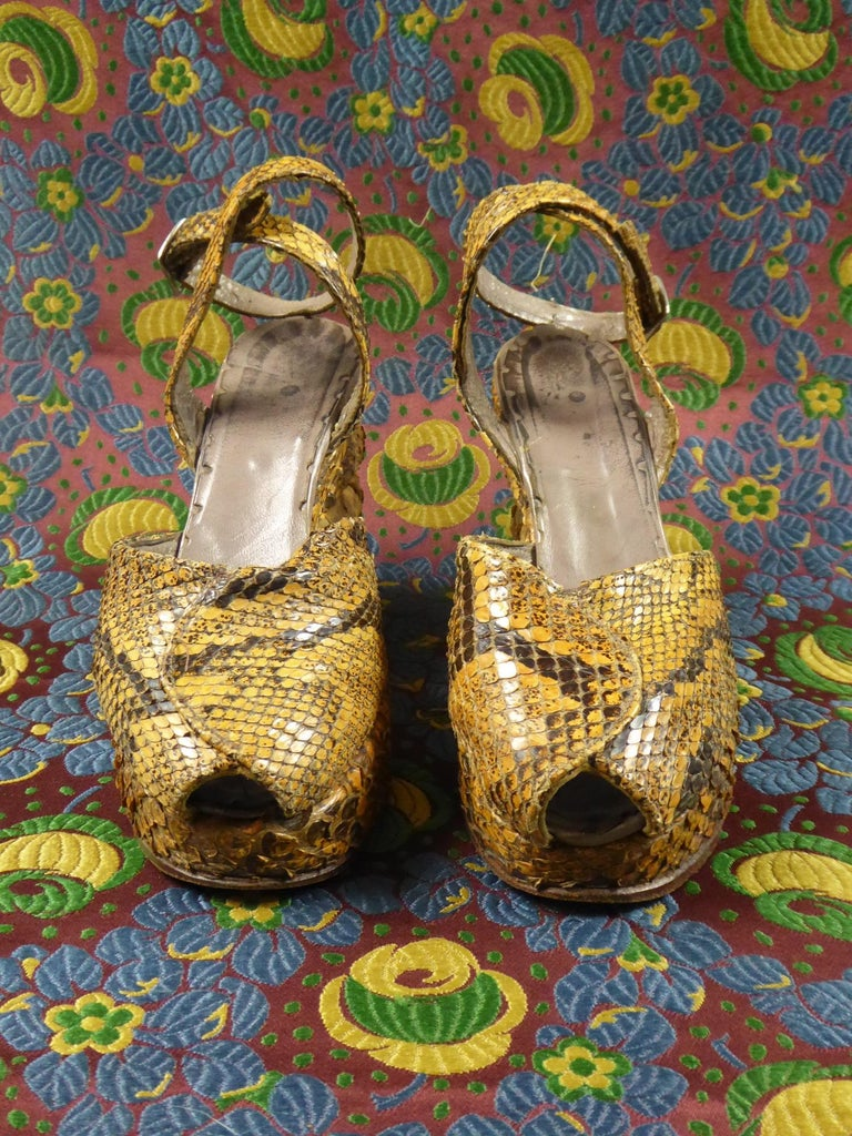 Circa 1940/1945 France  Rare pair of shoes with wedge heels fully covered with snake skin (?) from the 1940s of the Second World War. Shoes with open ends and crossed tabs at the ankle. Clever work of raised soles in the form of