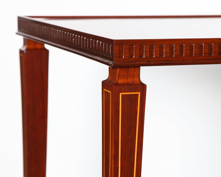 Pair of rosewood tables with shaped and tapered legs. Carved details around the outside edge of the top and inlaid light wood along the face of the legs. Beautiful brass cuffs and feet. These tables were found separately and therefore have slight