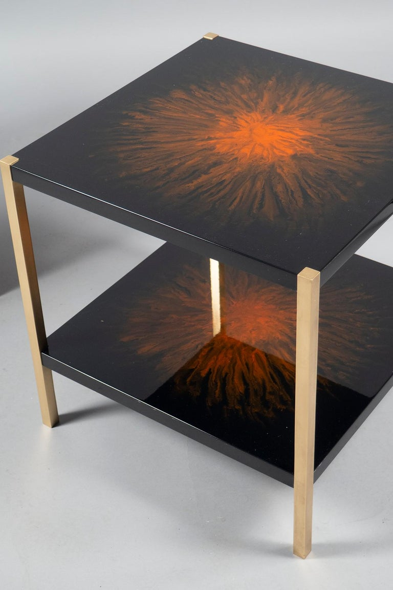 Square side tables with four brass legs holding two tops, decorated in black lacquer with an orange splat in the center. We have refreshed the lacquer, natural crackling will occur.