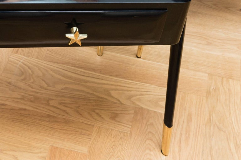 Elegant pair of side tables, Italy, circa 1950. Black shellac polished wood, organic shaped legs, solid polished brass legs, each have a glass shelf fixed with polished brass brackets and a drawer with a solid polished brass star handle. Each of the