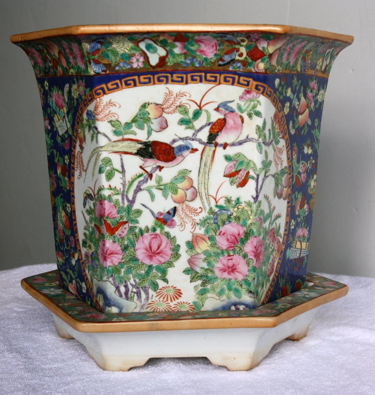 Pair of different sized, beautifully hand-painted jardinières with plates. Signature stamp on the bottom.  One large and one small. They both depict a garden scene with birds.    Dimensions of smaller jardinière: Diameter 6.5