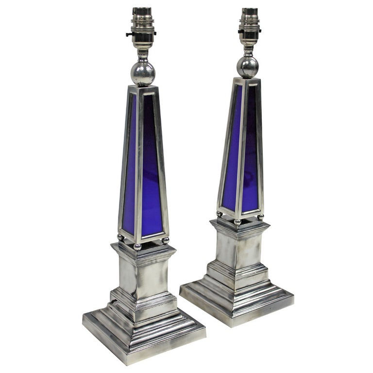 A pair of English silver plated obelisk lamps with blue glass panels.  These lamps are made to order for Ebury Trading.  These items are subjected to VAT.