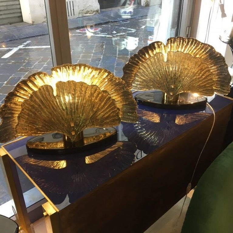 Pair of Murano glass shell lamps, silvered and gilt leaves, oval base in black Murano glass, one bulb per lamps.