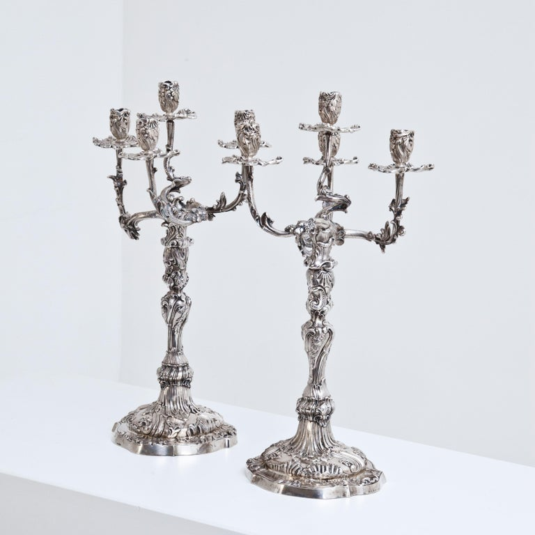 Pair of five-armed silver girandoles (2383g and 2485g) in rococo style with opulent rocailles and vine decoration. Stamped Mau, half moon crown, 800 and Dresden.