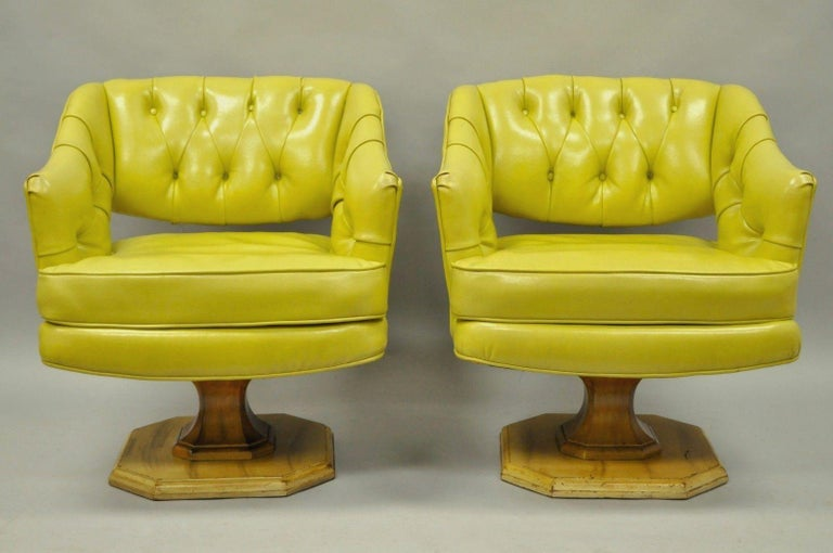 Great pair of vintage Mid-Century Modern greenish yellow tufted vinyl swivel club lounge by Silver-Craft Furniture Co. Item features solid wood frames, swivel pedestal bases, vinyl upholstery, button tufted backs, quality American craftsmanship,