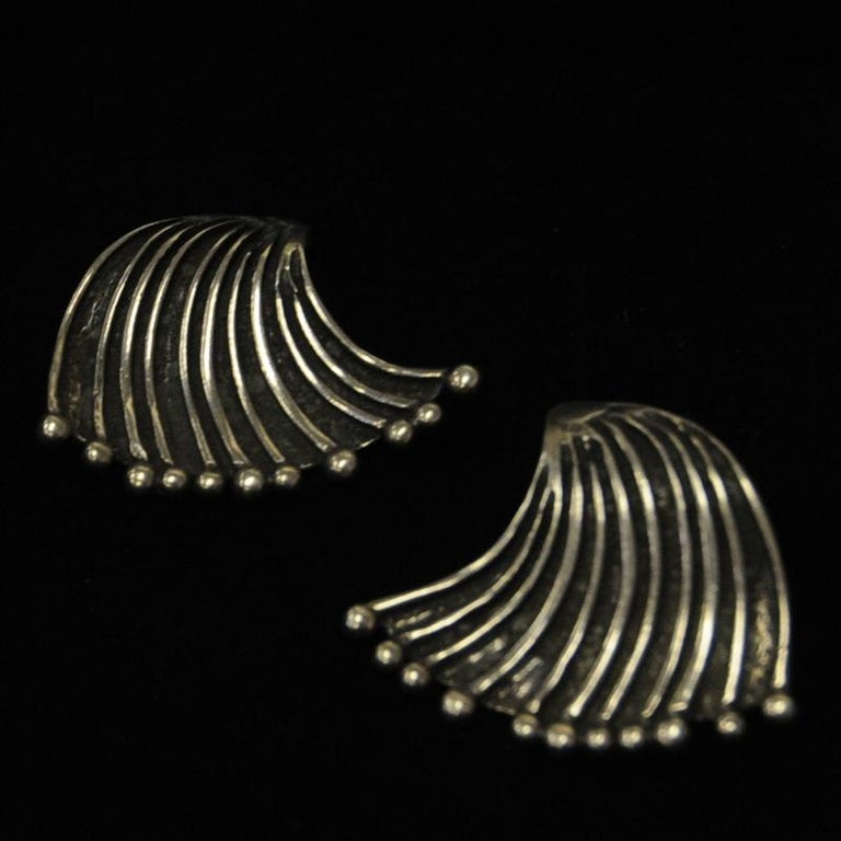 A lovely pair of vintage ear rings designed by Marianne Berg for Uni David Andersen in the 1960s, Norway. These ear rings has a waved triangel shape with clips on the back. They have stripe decoration with a little ball on the end. Beautiful