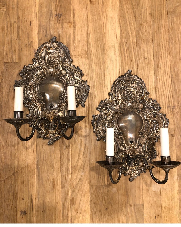 Pair of Paul Ferrante wall sconces. Silver plating with detailed relief backplates. Double S-curved arms.  Selling as a pair.