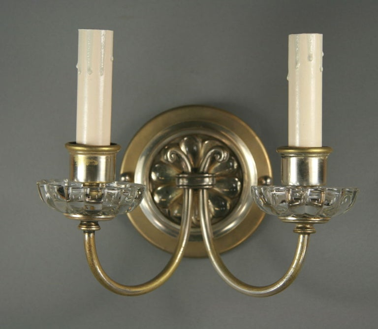 #2-409 a pair of silver plated double arm sconce having a crystal bobeches and backplate rosette.