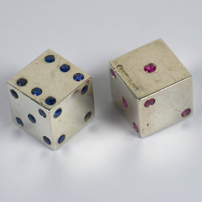 A fantastic pair of novelty French silver dice with the dots picked out in natural blue sapphires on one die, and natural rubies on the other. A lovely and unusual gambling set with great patina and a hefty feel in the hand. 1.5cm cubes.