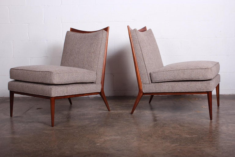 A pair of slipper chairs with walnut frames. Designed by Paul McCobb.