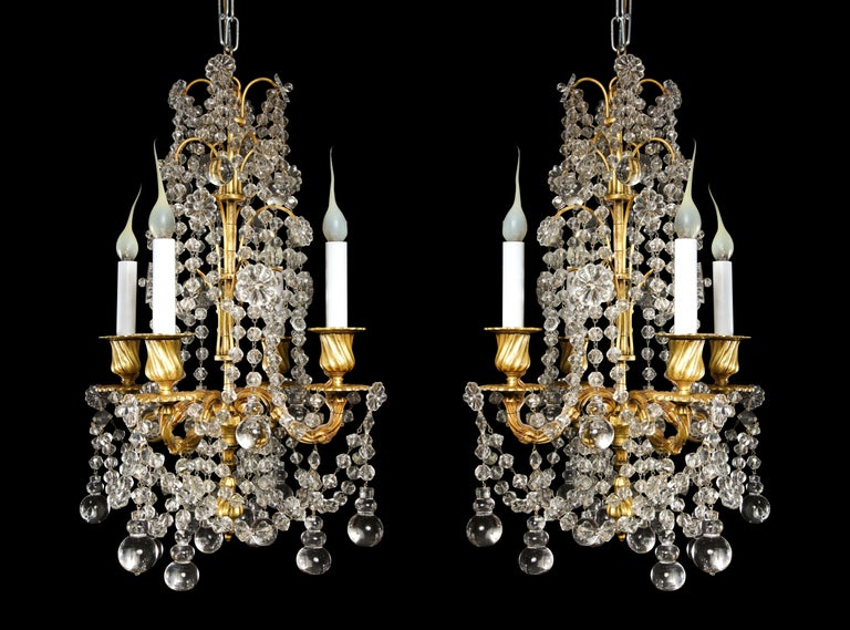 A pair of small antique French Louis XVI gilt bronze and crystal multi light chandeliers of fine quality embellished with crystal chains and further adorned with unusual round form crystal prisms.